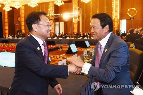 2016年8月27日、満面の笑みを浮かべ、韓国の柳一鎬(ユ・イルホ)経済副首相の手を両手で握る麻生太郎財務大臣