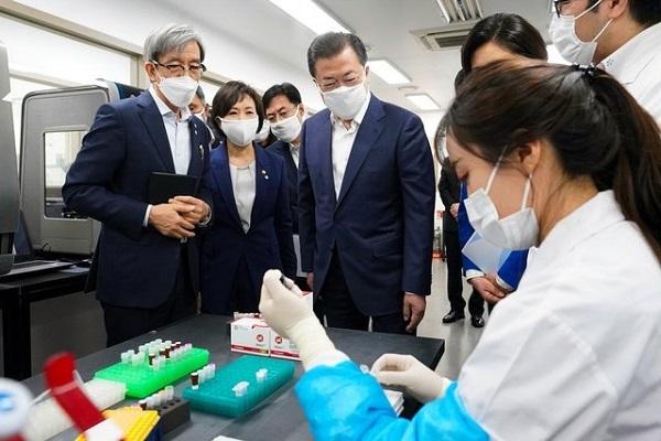 PCR検査を行うブースに入り、鼻から検体を採取される女性(左)=3月20日、ソウル、神谷毅撮影(画像を一部加工しています)