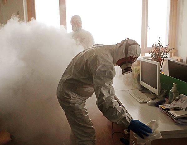 上海では防護服を着てオフィスを消毒する光景も…(ロイター)
