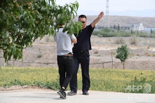 【写真】新疆ウイグル自治区アクトの村で、AFPのカメラマンを追い出そうとする男性