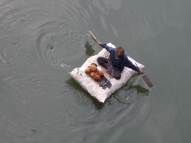 手製のボートに乗ってヤシの実を拾うじいちゃん_サイズ変更